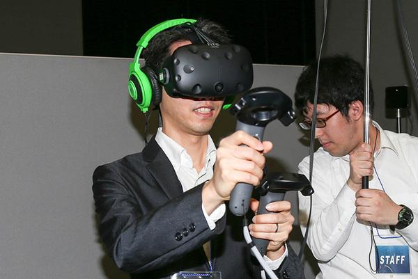 HMDを装着し、両手にコントローラを握って操作をする
